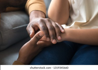 African american father dad holding hands of child as charity and support concept, children protection, kid adoption donation, black family love care connection, parenthood, upbringing, close up view