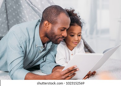 african american father and daughter lying on floor and reading together at home