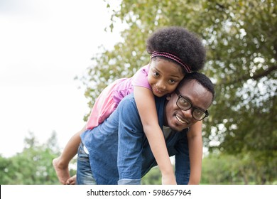 African American father and daughter playing and carrying on back in green park scene