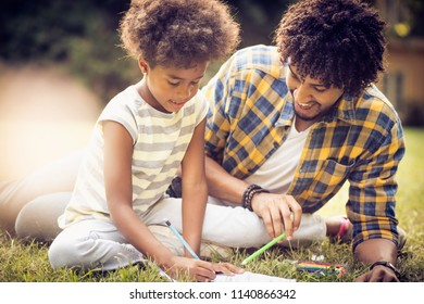 African American father and daughter writing together in nature