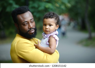 African American father is holding a cute little daughter.