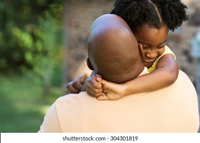 African American father hugging his daughter