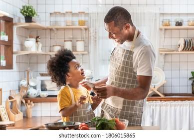 Afroamerikanischer Vater und kleiner Sohn, der beim Kochen in der Küche spielt und lacht. Schwarze Familie, die Spaß dabei hat, gesundes Essen zuhause zu bereiten. Brasilianischer Einziger Vater und Junge mit lächelndem Gesicht