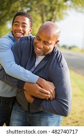 African American Father Playing  Football With His Son.