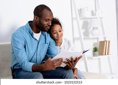 african american father reading book to daughter at home