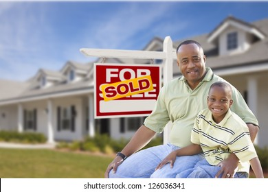 African American Father and Son In Front of Sold For Sale Real Estate Sign and New House.