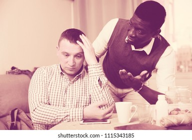 African American feeling guilty asking for forgiveness from his offended friend at home