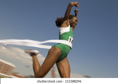 African American female athlete crossing finish line in race