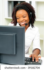 African American Female Call Center Agent Wearing A Telephone Headset Using A Computer