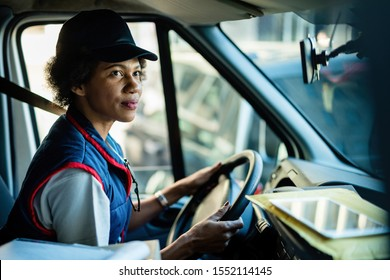 African American female courier driving delivery van in the city.