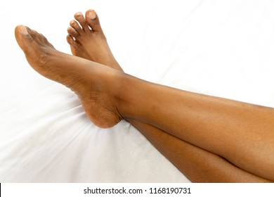 African American female feet legs heel of foot isolated on a white background  for medicine beauty relaxation and spa, health concept. Black woman's Long legs on white bed sheet