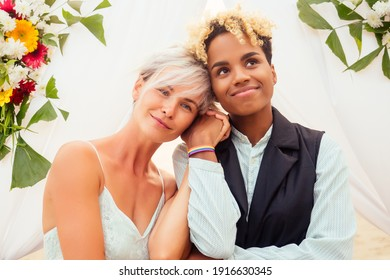 african american female groom in black suit and caucasian bride in dress in ceremony on tropical beach under wedding flover arch