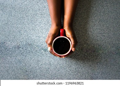 African American Female hands holding red cup of coffee espresso or cappuccino on on granite Kitchen counter-top. Black woman hands holding mug of hot drink for winter warmth refreshment concept