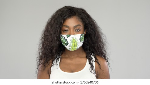 African American female in ornamental cloth mask looking at camera during epidemic against gray background