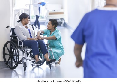 African American female patient in hospital wheelchair in corridor specialist care unit with medical staff