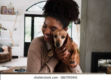 African American female smiling while snuggling cute puppy sitting at desk in modern kitchen.