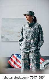 african american female soldier in military uniform with american flag on background
