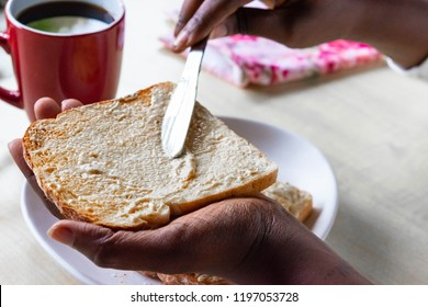 African American female spreading butter on toast with knife. Delicious butter and fresh homemade whole wheat organic toast bread in Black Woman's hands.