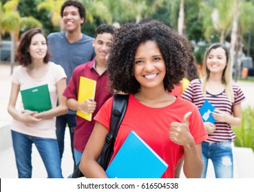 African american female student showing thumb with group of international students