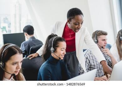 African American female supervisor training work to internatinal team in call center headquarter office