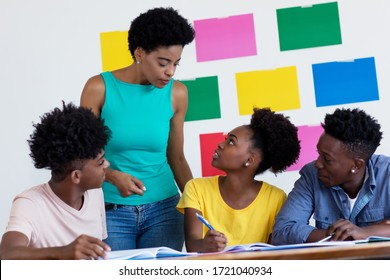 African american female teacher talking with students at classroom of school