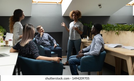 African american female team leader coach mentor talk to multiethnic work group business people in modern office instruct workers teach explain sales strategy at corporate meeting briefing training.