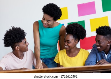 African american female tutor learning with students at classroom of school