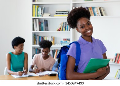 African american female young adult with students and teacher at classroom of university
