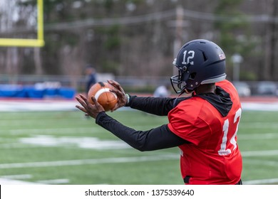 An African American football player is catching a ball