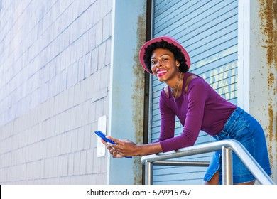 African American girl with afro hairstyle, wearing purple long sleeve T shirt, Denim skirt, pink hat, stands by doorway on street in New York, reads blue tablet computer, smiles. Color filtered effect