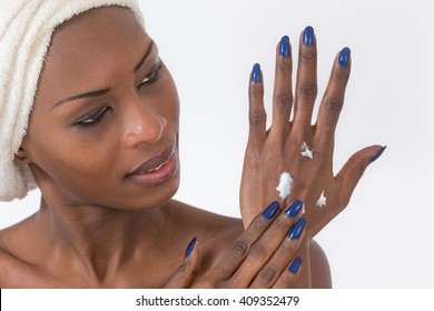 African American girl applying facial skincare product