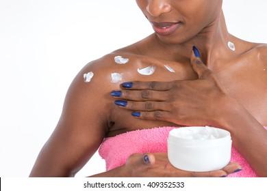 African American girl applying facial skincare product