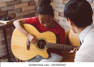 African American girl in casual outfit learning how to play guitar while sitting on couch near male tutor during music lesson