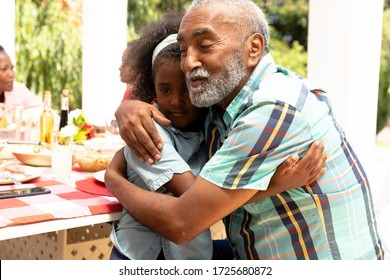 African American girl embracing with her grandfather during a family lunch in the garden on a sunny day.