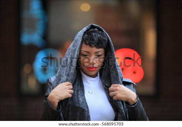 African American girl with head scarf, feeling cold, close portrait, the Afro-American woman with big lips, wearing the black leather jacket, curvy shaggy hair, beautiful bokeh, background wall