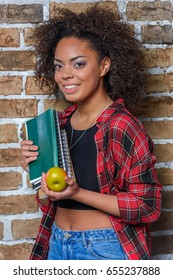 african american girl holding apple and notebooks while looking at camera