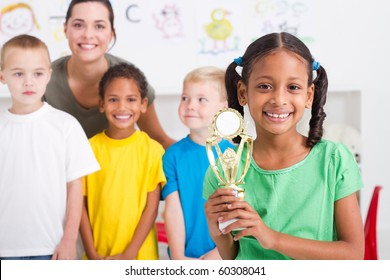african american girl holding a trophy in front of classmates