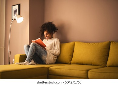 African american girl laughing while reading a funny book.
