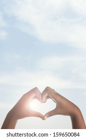 African american girl making heart shape with hands around sun.