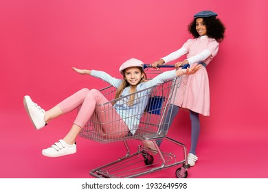 african american girl near excited friend riding in shopping trolley on pink