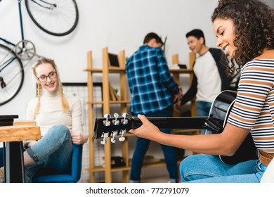 african american girl playing acoustic guitar for friends