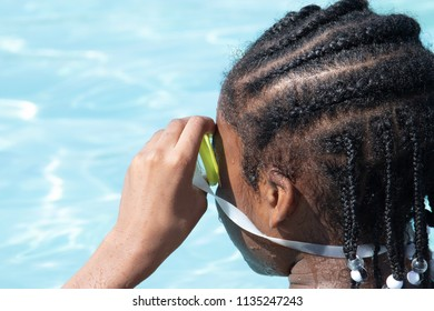 African American girl in the pool with her swim goggles