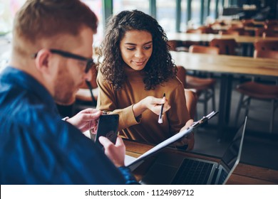 African american girl showing her boss business plan for signing communicating during meeting, back view of male employee reading report in folder of skilled colleague consulting about working tasks