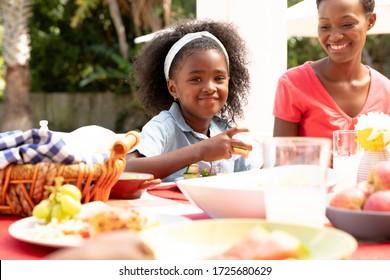 Niña afroamericana sonriendo y mirando a una cámara durante un almuerzo familiar en el jardín en un día soleado.