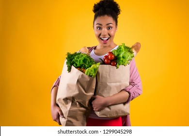 African American girl in sweater with groceries bags smiling isolated.