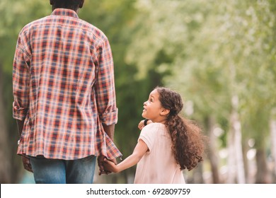 african american granddaughter holding hands with grandfather and walking in park