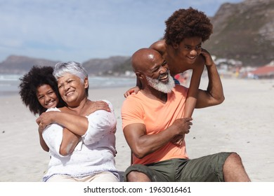 African american grandparents and grandchildren hugging while siting on the beach. travel vacation summer beach concept