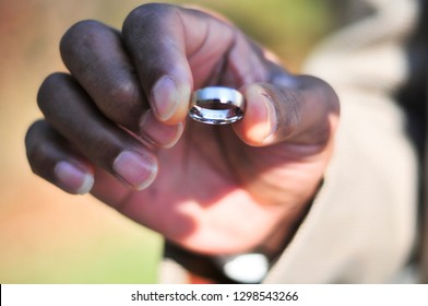African American groom holding wedding ring with inscription at ceremony