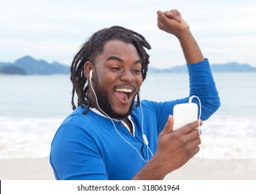 African american guy with dreadlocks listening to music at beach