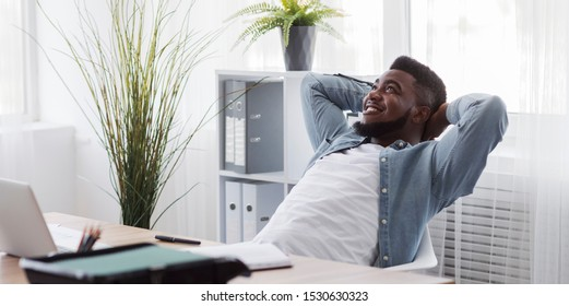 African american guy resting from office work, leaning back on chair in modern office, panorama with copy space